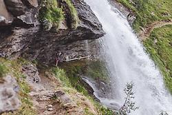 THEMENBILD - eine junge Frau steht hinter einem Wasserfall. Der Wasserfallwanderweg führt hinter dem Wasserfall durch. Das frische Quellwasser ergießt sich über einen großen Felsen, aufgenommen am 28. Juli 2019 in Fusch a. d. Grossglocknerstrasse, Oesterreich // a young woman stands behind a waterfall. The waterfall hiking trail leads behind the waterfall. The fresh spring water pours over a large rock, in Fusch a. d. Grossglocknerstrasse, Austria on 2019/07/28. EXPA Pictures © 2019, PhotoCredit: EXPA/Stefanie Oberhauser