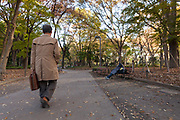 A salaryman or male office worker walks past a homeless man sleeping on a bench in a Chuo Park in Shinjuku, Tokyo, Japan. Tuesday November 29th 2016