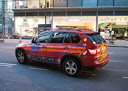 © London News Pictures. 30/04/2015. The police vehicle driving away from the restaurant with its emergency lights turned off. A member of the Metropolitan police buying three drinks, from a McDonald's in Victoria, London while is colleagues wait in a police vehicle, parked on double yellow lines and using emergency lights. The police vehicle was blocking one lane of a busy road leading from Westminster through central Victoria. When the officer returned to the police vehicle the emergency lights were turned off.  Photo credit: LNP