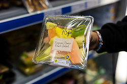 "© Licensed to London News Pictures. 19/12/2014. London, UK. A customer holds a Marks and Spencer fruit salad costing 10p in the Community Shop. The Community Shop opened this week in Gipsy Hill, South London and is a ""social supermarket"", which sells heavily-discounted surplus food that would otherwise be thrown away. Food is received from retail brands such as Marks & Spencer, Asda, Tesco, Innocent and Muller and many more. The shop works on a membership basis only, serving residents who are on income support and aimed at people who are in work, but low waged and for those working hard to find a job. Photo credit : Vickie Flores/LNP"