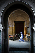 A veiled woman walks past the ornate doorway to the Bou Inania Medersa in Fes El-Bali, Morocco.