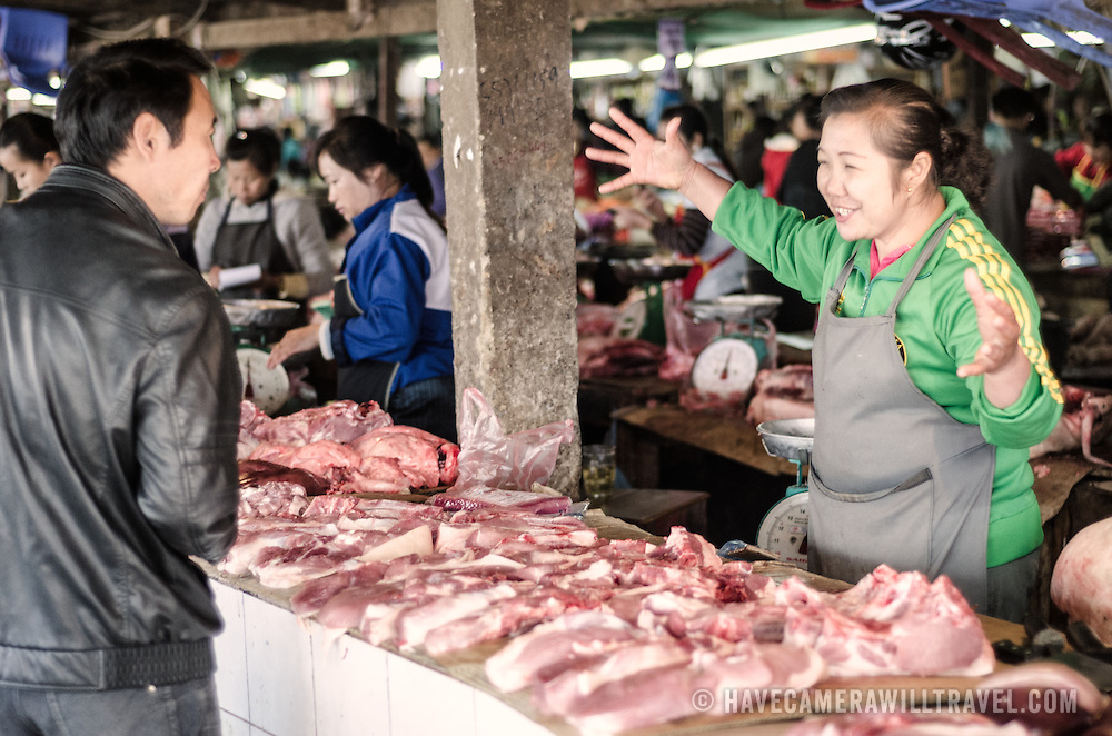 A butcher talks with a customer at the large and bustling morning market in Phonsavan in northeastern Laos. The market has no refrigeration, so vendors must accurately predict how much perishable food to put out on any given day. The people of the region are predominantly of Hmong ethnicity.