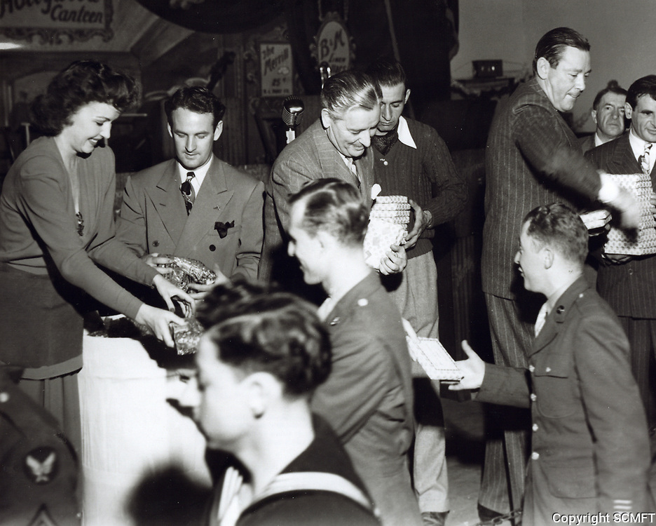 1944 (L to R) Benita Hume, unknown, Ronald Colman and Herbert Marshall hand out Christmas gifts at the Hollywood Canteen