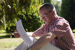 Man sitting in the sunshine reading notes from Mental Health conference,