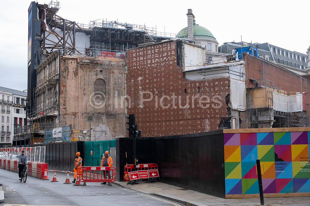Large construction site of a whole block due for redevelopment just behind the famous electronic advertising boards at Piccadilly Circus on 1st July 2020 in London, United Kingdom. The site, which is on a massive scale, reveals the inner brickwork of the buildings exposed.