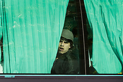 EDITORS ADVISORY - YOUTH PICTURED MAY BE UNDER 16© Licensed to London News Pictures. 26/10/2016. London, UK. A youth looks out from a coach window as he arrives at a Home Office immigration centre in Croydon.  Hundreds of unaccompanied children are being brought over from France as the French government closes the Calais jungle camp. Photo credit: Peter Macdiarmid/LNP