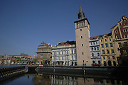 Buildings along the Prague River with the Town Hall Tower in Prague, Czech Republic.
