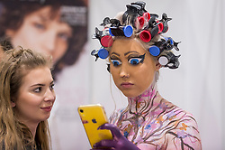 © Licensed to London News Pictures. 25/02/2019. LONDON, UK. A make-up artist checks her Disney-inspired bodypaint on a model at the Warpaint Zone at Professional Beauty, the UK's largest beauty and spa trade show, taking place at Excel London in Docklands.  Photo credit: Stephen Chung/LNP