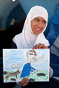 Tunisia 2011. Remada camp for Libyan refugees - around 300 families are there (most Libyans are with host families).<br /> 16 year old from Nalut holding a picture she has drawn of Gaddafi, writing says 'Go Away'.