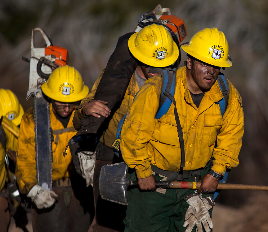 Firefighters walk out of the active burning area of the Soberanes Fire near Chews Ridge in the Los Padres National Forest near Big Sur, Calif. on Sept. 24, 2016.
