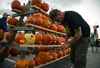 Johnny Rogers joins in to help light jack o lanterns from Woodland Heights Elementary School displayed at Bank of NH during Pumpkin Fest Saturday evening.  (Karen Bobotas/for the Laconia Daily Sun)