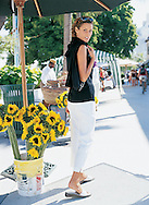 Lifestyle photography depict Sylvina walking throgh the market by some sunflowers.