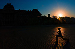 A female athlete stretches before a run in front of the Royal Palace in Brussels, Belgium. (Photo © Jock Fistick)