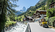 The Matterhorn rises above a horse-drawn carriage along the Matter Vispa (a river tributary of the Rhone). Zermatt, Pennine Alps, Switzerland, Europe.