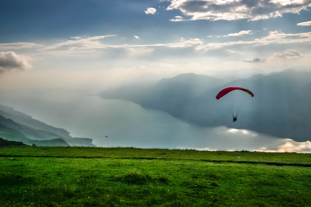A paraglider on Garda Lake, Italy. Taking off from the Western side one arrives on the upright of the lake over 100 m of elevation admiring all lake Garda.