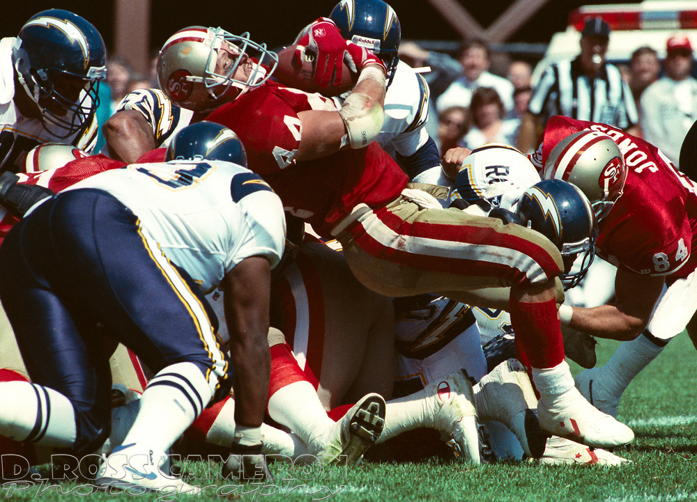 San Francisco 49ers fullback Tom Rathman (44) is stacked up by the San Diego Chargers defense during an NFL football game, Sunday, Sept. 8, 1991 at Candlestick Park in San Francisco. The 49ers won, 34-14. (Photo by D. Ross Cameron)