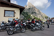 A group of bikers rest up on Passo Falzarega (Pass) in south Tyrol, Italy. Cyclist groups as well as biker clubs ascend the pass (alt 2.105m) as part of their tours of the Dolomites - one of the must-do climbs on two and four wheels. The Falzarego Pass is a high mountain pass in the province of Belluno in Italy and connecting Andráz and Cortina d'Ampezzo. The name Falza Rego means false king in ladin and refers to a king of the Fanes, who was supposedly turned to stone for betraying his people.