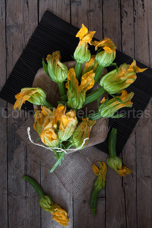 Flowering baby zucchini or courgette, photographed from above, on wood background.