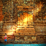 A young vietnamese girl stands in front of a weathered wall, Po Nagar temple, Nha Trang area, Vietnam, Southeast Asia