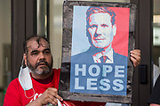 A man holds a sign bearing an image of Labour Party leader Sir Keir Starmer at a protest lobby outside the partys headquarters by supporters of left-wing groups on 20th July 2021 in London, United Kingdom. The lobby was organised to coincide with a Labour Party National Executive Committee meeting during which it was asked to proscribe four organisations, Resist, Labour Against the Witchhunt, Labour In Exile and Socialist Appeal, members of which could then be automatically expelled from the Labour Party.