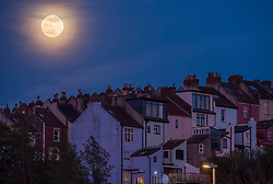 © Licensed to London News Pictures; 26/04/2021; Bristol, UK. A waxing full moon is seen above rooftops in Bristol. This month's full moon will fall on 27 April, the fourth full moon of 2021, and is called the pink supermoon, thought to have been named by a group of Native Americans after the pink moss (creeping phlox) that grows during this time of the year. The supermoon is set to pass within 358,000km from Earth, appearing a 30 per cent brighter and 14 per cent larger than some previous full Moons. Photo credit: Simon Chapman/LNP.