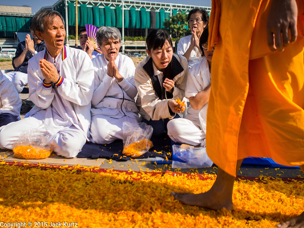 """02 JANUARY 2015 - KHLONG LUANG, PATHUM THANI, THAILAND: People pray as monks walk past them at Wat Phra Dhammakaya on the first day of the 4th annual Dhammachai Dhutanaga (a dhutanga is a """"wandering"""" and translated as pilgrimage). More than 1,100 monks are participating in a 450 kilometer (280 miles) long pilgrimage, which is going through six provinces in central Thailand. The purpose of the pilgrimage is to pay homage to the Buddha, preserve Buddhist culture, welcome the new year, and """"develop virtuous Buddhist youth leaders."""" Wat Phra Dhammakaya is the largest Buddhist temple in Thailand and the center of the Dhammakaya movement, a Buddhist sect founded in the 1970s.   PHOTO BY JACK KURTZ"""