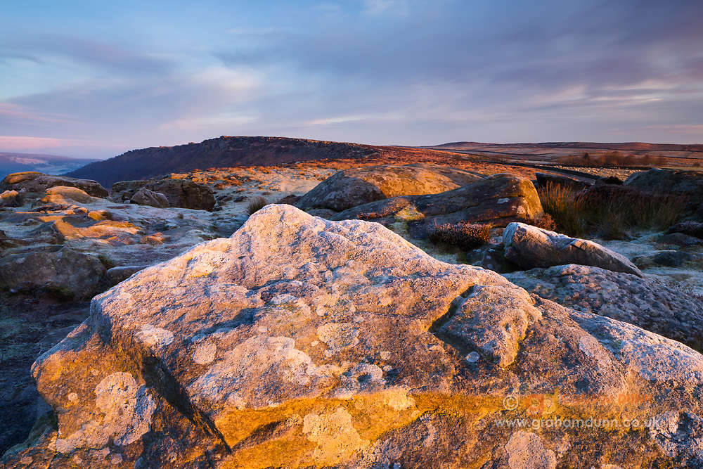 Dawn light warms this frosty scene atop Baslow Edge in the eastern Peak District. The triangular rock points towards a distant Curbar Edge. Winter. Derbyshire, England, UK.
