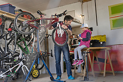 Father and daughter repairing bicycle in garage