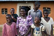 Margaret Nakazi with her 5 children standing in front of the family farm-house. Her husband has recently passed away, she supplies all the family food.