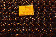 In the underground winecellar that is an old chalk quarry: thousands (4047) of bottles aging in under a vault, Champagne Ruinart, Reims, Champagne, Marne, Ardennes, France, low light grainy grain