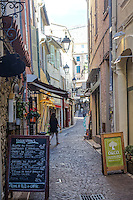 Colorful shops and restaurants line a narrow pedestrian street in the old quarter of Antibes on the French Riviera. A girl wearing a black sweater walks up the stone paved street.
