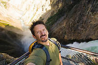 A self portrait of a man standing at a overlook above Yellowstone Falls, Yellowstone National Park, Wyoming, USA.