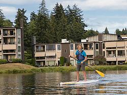 United States, Washignton, Bellevue, man stand-up paddleboarding in Meydenbauer Bay  MR