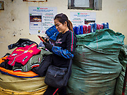 "22 DECEMBER 2017 - HANOI, VIETNAM: A worker checks her smart phone in the wholesale clothes and fabric section of Dong Xuan Market in the old quarter of Hanoi. The old quarter is the heart of Hanoi, with narrow streets and lots of small shops but it's being ""gentrified"" because of tourism and some of the shops are being turned into hotels and cafes for tourists and wealthy Vietnamese.    PHOTO BY JACK KURTZ"