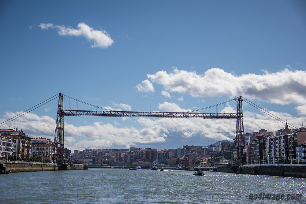 The Vizcaya Bridge was built to connect the two banks which are situated at the mouth of the Nervion River. It is the world's oldest transporter bridge and was built in 1893, designed by Alberto Palacio, one of Gustave Eiffel's disciples. The Engineer Ferdinand Joseph Arnodin was in charge, and the main financier of the project was Santos Lopez de Letona. It was the solution given by the engineer to the problem of connecting the towns of Portugalete and Getxo without disrupting the maritime traffic of the Port of Bilbao and without having to build a massive structure with long ramps. Palacio wanted to design a bridge which could transport passengers and cargo, and that could allow ships to go through. Palacio's shuttle bridge was adequate and could be built for a reasonable price.<br /> <br /> The service was only interrupted once, for four years, during the Spanish Civil War, when the upper section was dynamited. From his house in Portugalete, Palacio saw his masterpiece partially destroyed just before his own death. On July 13, 2006, the Vizcaya Bridge was declared a World Heritage Site by UNESCO. In Spain, it is the only monument in the Industrial Heritage category. UNESCO considers the bridge to be a perfect combination of beauty and functionality. It was the first to use a combination of iron technology and new steel cables which began a new form of constructing bridges which was later imitated throughout the world.