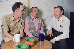 Three men with learning disabilities sitting together in community centre talking and laughing,