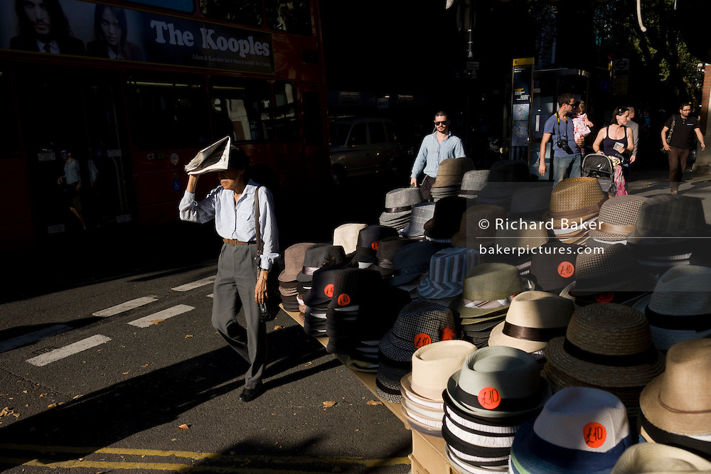 Londoner shields his eyes in afternoon sun instead of buying a hat while alongside a hat market stall.