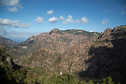 Landscape view from the town of Evisa, Corsica, France. Evisa is a central location for walkers who come to walk to the Gorges de Spelunca which are below in the distance. Corsica is an island in the Mediterranean and one of the 18 regions of France. It is located southeast of the French mainland and west of the Italian Peninsula.