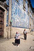 An elderly woman and man walk past the Capela Das Almas in Porto, Portugal. The church is clad in ornate azulejo tiles that depict scenes from the lives of various saints, including the death of St Francis and the martyrdom of St Catherine.