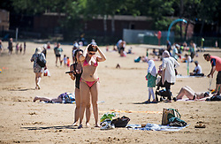 © Licensed to London News Pictures. 09/06/2021. London, UK. Members of the public relax in the hot weather at Ruislip Lido in Ruislip, north west London on what is expected to be one of the hottest days of the year so far. Photo credit: Ben Cawthra/LNP