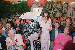 Mature lesbian wedding ceremony with partners walking down aisle smiling at wedding guests,