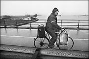 Nederland, Leeuwen, 01-02-1995Eind januari, begin februari 1995 steeg het water van de Rijn, Maas en Waal tot record hoogte van 16,64 m. bij Lobith. Een evacuatie van 250.000 mensen was noodzakelijk vanwege het gevaar voor dijkdoorbraak en overstroming. op verschillende zwakke punten werd geprobeerd de dijken te versterken met zandzakken. Hier verlaat een man op de fiets als een van de laatsten het gebied richting wijk bij duurstede. Hij heeft in de tas zijn duiven meegenomen.Late January, early February 1995 increased the water of the Rhine, Maas and Waal to a record high of 16.64 meters at Lobith. An evacuation of 250,000 people was needed because of flood risk. At several points people tried to reinforce the dikes with sandbags.Foto: Flip Franssen/Hollandse Hoogte