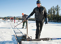 Norman Lyford guides the ice slabs up the channel for Camp Manager John Jurczynski to load the ramp into awaiting trucks during the Rockywold Deephaven Ice Harvest on Tuesday afternoon.  Mr. Lyford has been working the annual ice harvest for 70 years.  (Karen Bobotas/for the Laconia Daily Sun)