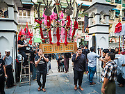 23 OCTOBER 2015 - YANGON, MYANMAR: Shia men carry a representation of the coffin of Hussein ibn Ali into Mogul Mosque in Yangon during an Ashura procession. Ashura commemorates the death of Hussein ibn Ali, the grandson of the Prophet Muhammed, in the 7th century. Hussein ibn Ali is considered by Shia Muslims to be the third imam and the rightful successor of Muhammed. He was killed at the Battle of Karbala in 610 CE on the 10th day of Muharram, the first month of the Islamic calendar. According to Myanmar government statistics, only about 4% of the population is Muslim. Many Muslims have fled Myanmar in recent years because of violence directed against Burmese Muslims by Buddhist nationalists.    PHOTO BY JACK KURTZ