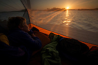 A boy (7 years old)  waking up at sunrise in tent on the Hell's Bay Chickee camping platform in the mangroves.  .Hell's Bay Canoe Trail, Everglades National Park..