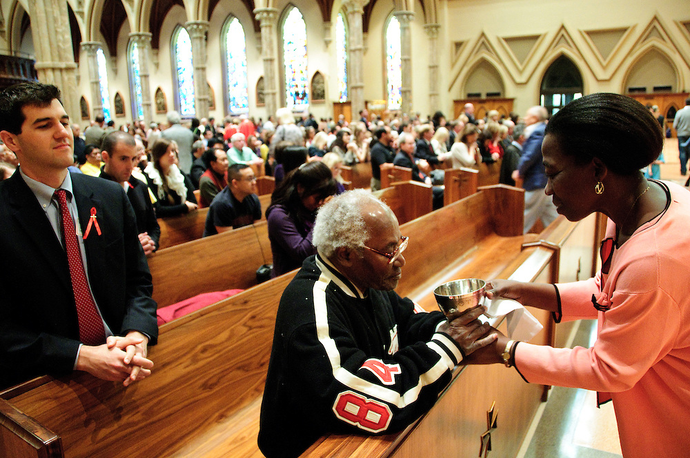"""Martine Monney (R) shares communion with Michael Herard during the 78th Annual Votive Mass of the Holy Spirit, or """"Red Mass"""" is celebrated at Holy Name Cathedral in Chicago. September 30, 2012 l Brian J. Morowczynski~ViaPhotos..For use in a single edition of Catholic New World Publications, Archdiocese of Chicago. Further use and/or distribution may be negotiated separately. Contact ViaPhotos at 708-602-0449 or email brian@viaphotos.com."""