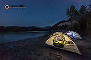 Tents glow as night falls along the Flathead River in the Flathead National Forest, Montana, USA