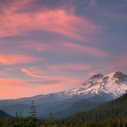 A summertime sunset over wildflowers and Mount Rainier national Park.