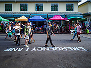"""01 AUGUST 2018 - BANGKOK, THAILAND:     Tourists walk past """"Emergency Lane"""" recently stenciled on Khao San Road in Bangkok. Street market venders are not supposed to set up in the emergency lane areas. Khao San Road is Bangkok's original backpacker district and is still a popular hub for travelers, with an active night market and many street food stalls. The Bangkok municipal government went through with it plans to reduce the impact of the street market on August 1 because city officials say the venders, who set up on sidewalks and public streets, pose a threat to public safety and could impede emergency vehicles. Venders are restricted to working from 6PM to midnight and fewer venders will be allowed to set up on the street. It's the latest in a series of night markets and street markets the city has closed.    PHOTO BY JACK KURTZ"""