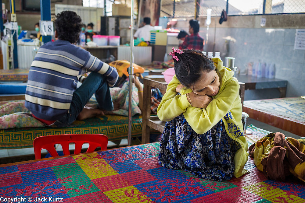 05 MARCH 2014 - MAE SOT, TAK, THAILAND: A woman who lives just across the Thai-Burma border waits to see a medic in a ward at the Mae Tao Clinic. She came to the clinic complaining of stomach pains. The Mae Tao Clinic provides  healthcare to over 150,000 displaced Burmese per year and is the leading healthcare provider for Burmese along the Thai-Myanmar border. Reforms in Myanmar have alllowed NGOs to operate in Myanmar, as a result many NGOs are shifting resources to operations to Myanmar, leaving Burmese migrants and refugees in Thailand vulnerable.     PHOTO BY JACK KURTZ